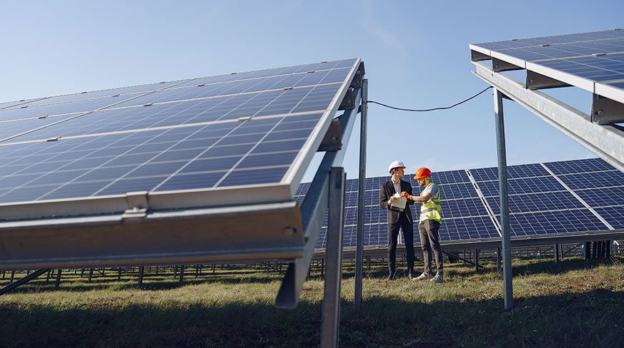 Canva - Engineer interacting with colleague standing near solar panels in countryside - optimised community solar