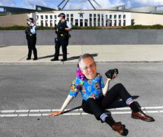 An Extinction Rebellion activist wears a mask depicting Australian Prime Minister Scott Morrison blocks the road during a protest outside Parliament House in Canberra. (AAP Image/Lukas Coch)